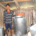 1 boy standing beside metal drum (stove)