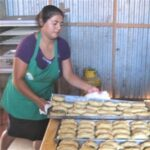 1 woman putting tray of buns on table - large